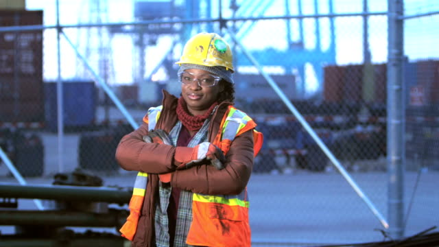 African-American woman at shipping port, arms crossed