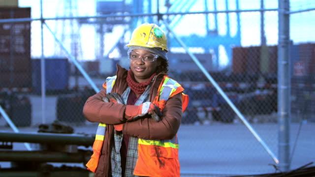 vídeos y material grabado en eventos de stock de mujer afroestadounidense en el puerto de embarque, brazos cruzados - obrero de la construcción