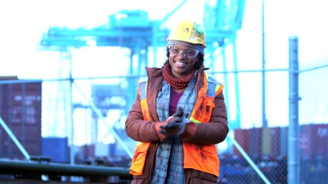 vídeos de stock e filmes b-roll de african-american woman at shipping port, rubbing hands - dureza