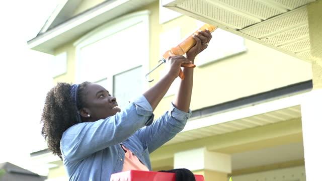 vídeos y material grabado en eventos de stock de mujer afroamericana haciendo mantenimiento en el hogar - reparador