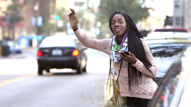 African-American woman hailing a taxi video