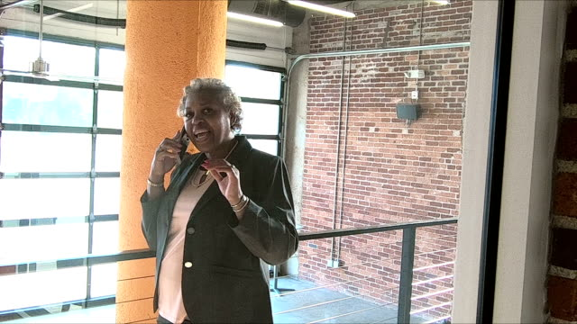 African-American woman in city on phone in building