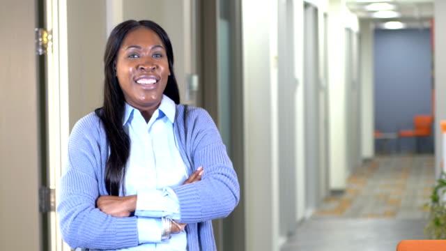 vídeos y material grabado en eventos de stock de mujer afroamericana en el pasillo de la oficina - encuadre cintura para arriba