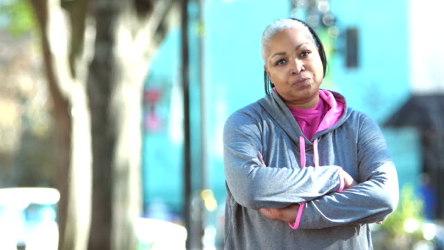 african-american woman in sweatshirt, crossing arms - guardare fisso video stock e b–roll