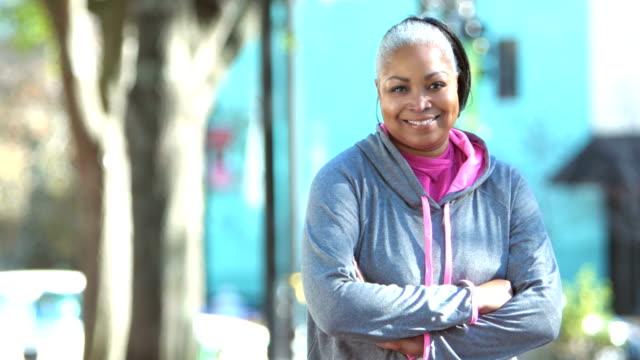 African-American woman in sweatshirt, crossing arms
