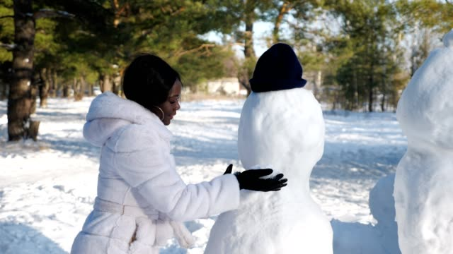 African-American woman makes snowman among winter nature