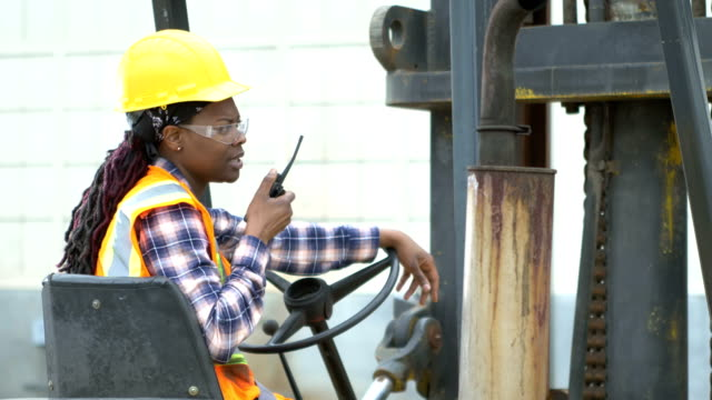 African-American woman operating forklift A young woman in her 20s operating a forklift. She is wearing safety goggles, a hardhat and reflective vest, sitting in the driver's seat. She is an African-American woman with long, braided hair in a traditionally male occupation. She is talking on a walkie-talkie with a serious expression. occupational safety and health stock videos & royalty-free footage
