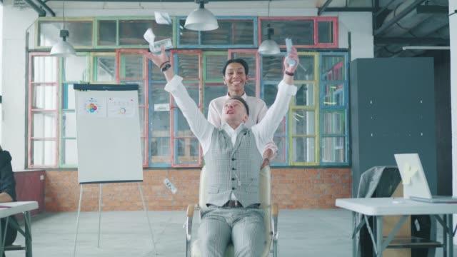 Die Afroamerikanerin rollt einen männlichen Kollegen in einen Bürostuhl. Ein Mann wirft Geld, sie lachen und haben Spaß. Mitarbeiter fahren auf einem Stuhl um das Büro herum. Co-Working. Büroleben. Kreatives Interieur. – Video