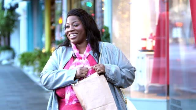 afroamerikanerin kauft in der stadt ein - übergrößen model stock-videos und b-roll-filmmaterial