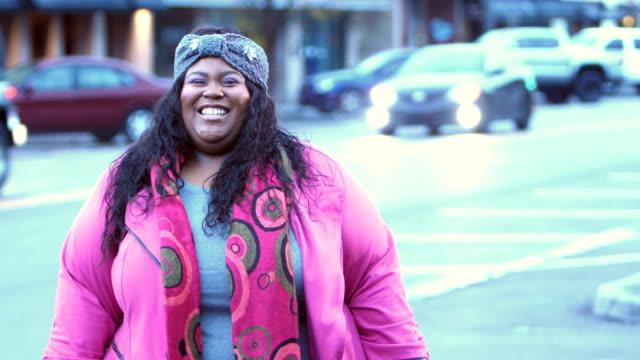 afroamerikanerin steht auf stadtstraße - übergrößen model stock-videos und b-roll-filmmaterial