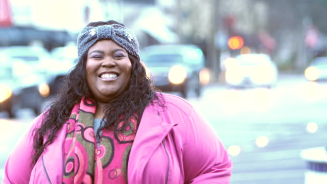 African-American woman standing on city street A mid adult African-American woman in her 30s standing in the city with traffic driving by on the street behind her, smiling at the camera. She has a full figure. plus size model stock videos & royalty-free footage