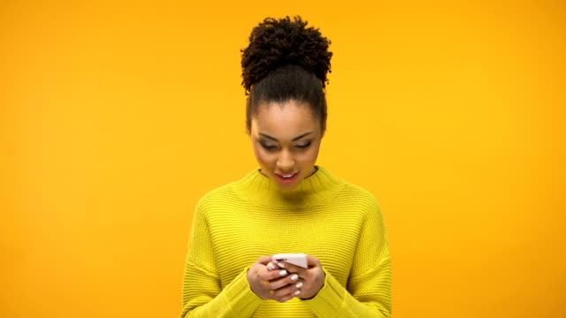 african-american woman using smartphone, excited about job acceptance e-mail - telefon przenośny filmów i materiałów b-roll