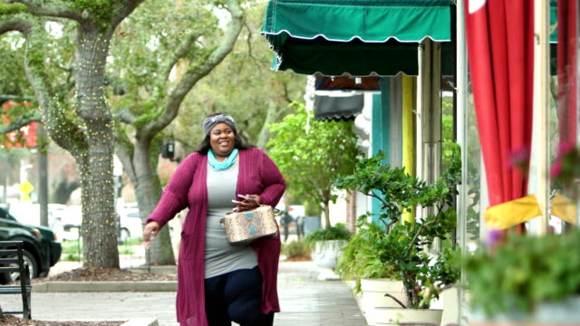 African-American woman walking by storefronts A mid adult African-American woman in her 30s walking down a sidewalk lined with shops. She is a large, full-figured woman. plus size model stock videos & royalty-free footage