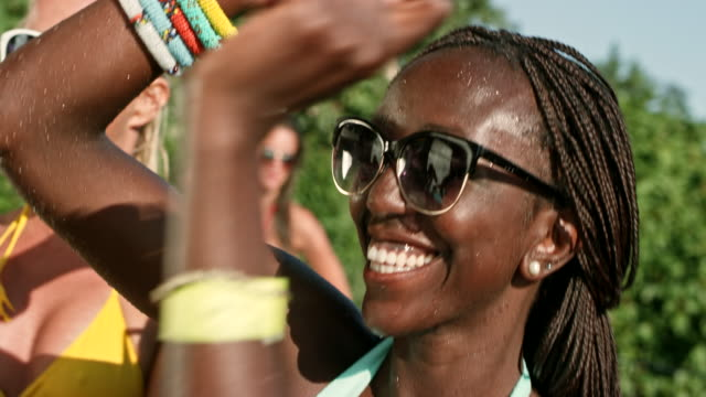 SLO MO African-American woman wearing sunglasses dancing in her bathing suit at a pool party video