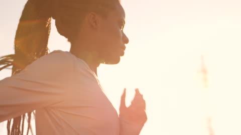 günbatımında çalışan örgülü saçlı slo mo ts afrikalı-amerikalı kadın - dişiler stok videoları ve detay görüntü çekimi