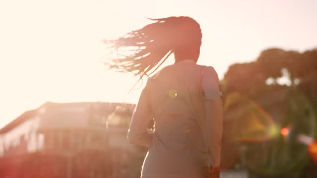 SLO MO African-American woman with long braided hair running in the stadium at sunset video