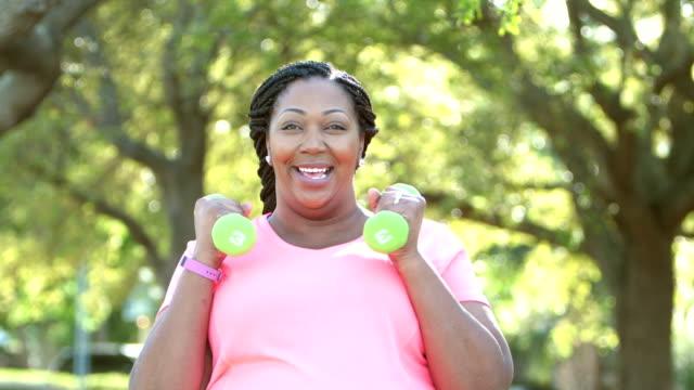 vídeos de stock, filmes e b-roll de mulheres afro-americanas, exercitando, com pesos de mão - camiseta preta