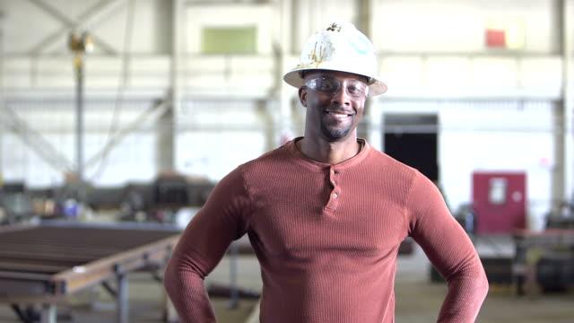 vídeos de stock e filmes b-roll de african-american worker in factory, walks up to camera - dureza