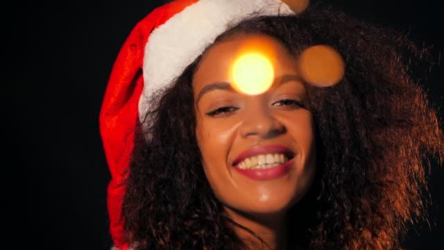stockvideo's en b-roll-footage met afrikaans-amerikaanse jonge vrouw in partij jurk holding bengalen wonderkaarsen brand en dansen op black lights achtergrond. meisje in kerstmuts op nieuwjaar of kerstmis. slow motion - {{asset.href}}
