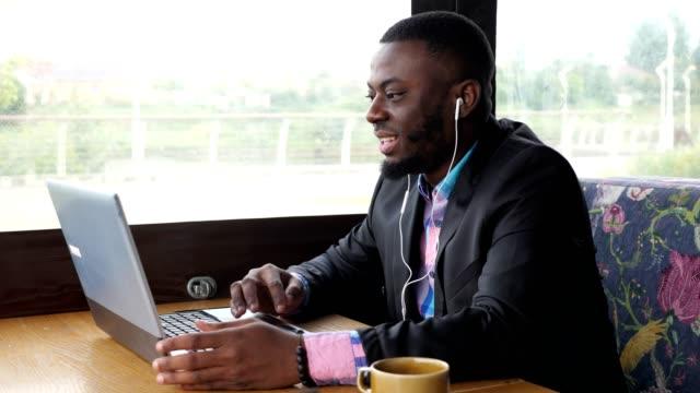 afro amerikan siyah adam konuşmaları bilgisayarda kulaklıyla video sohbet kafede oturuyor. - kulak i̇çi kulaklık stok videoları ve detay görüntü çekimi