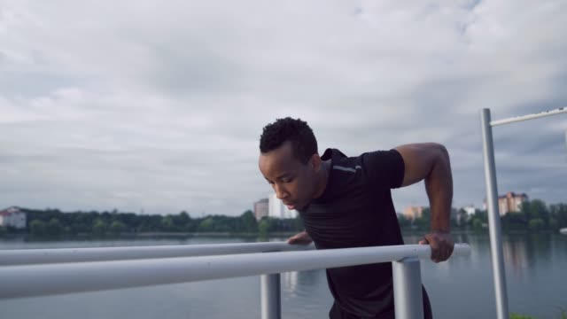 Afro american guy workout on dips bars near the city lake