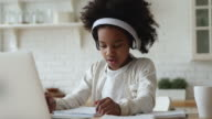 istock Afro american kid girl wearing headphones studying online from home 1220763101