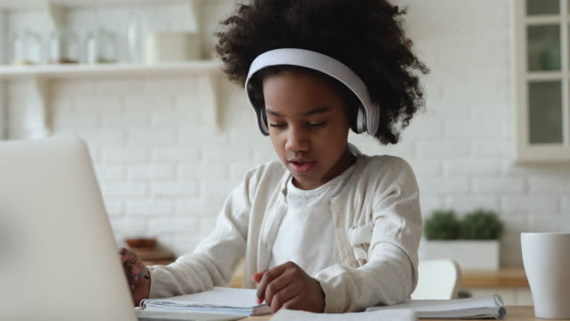 Afro american kid girl wearing headphones studying online from home