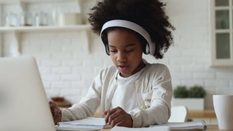 Afro american kid girl wearing headphones studying online from home Afro american kid girl school pupil wearing headphones studying online from home watching web class lesson or listening tutor by video call elearning on pandemic isolation. Children remote education. child stock videos & royalty-free footage