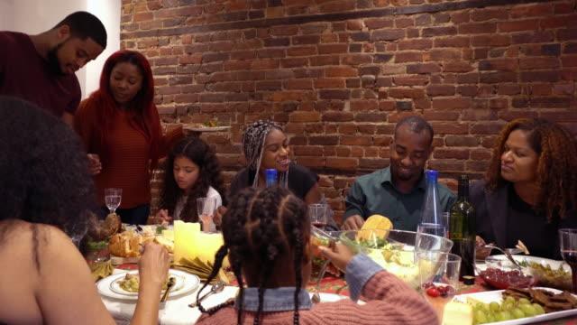 vídeos y material grabado en eventos de stock de afro americano gran familia compartiendo pavo comensal para acción de gracias multigeneraciones - thanksgiving turkey