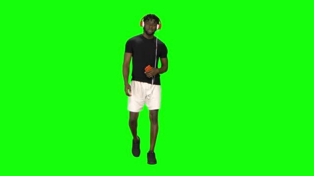 vídeos de stock e filmes b-roll de afro american man is walking in big red headphones, chooses music on mobile phone and moves to rhythm at green screen - teeshirt template