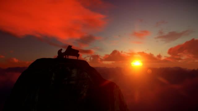 vídeos de stock, filmes e b-roll de afro americana pianista tocando no topo de uma montanha acima de nuvens contra o belo pôr do sol, drone vista 4k - arte, cultura e espetáculo