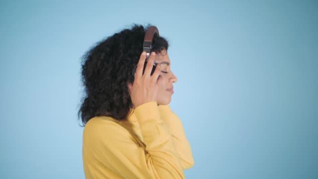 stockvideo's en b-roll-footage met afro-amerikaanse vrouw luisteren naar muziek op de kleurrijke blauwe achtergrond. verliefd op melodieën. meloman. slow motion - afro amerikaanse etniciteit
