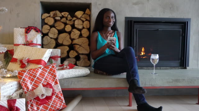 Video Afro American Young Woman texting Alone Home By Fireplace and Christmas Tree