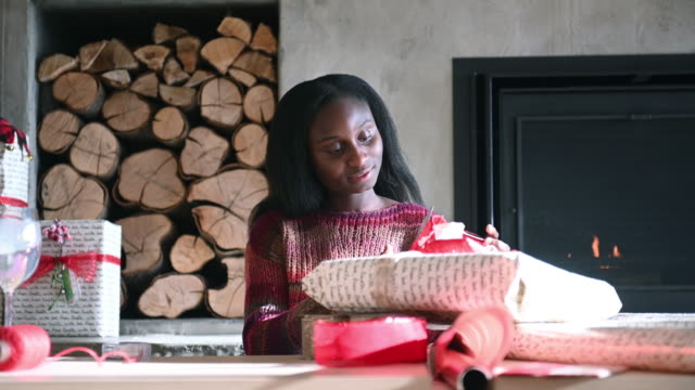 Video Afro American Young Woman Wrapping Christmas Gift Alone Home By Fireplace and Christmas Tree