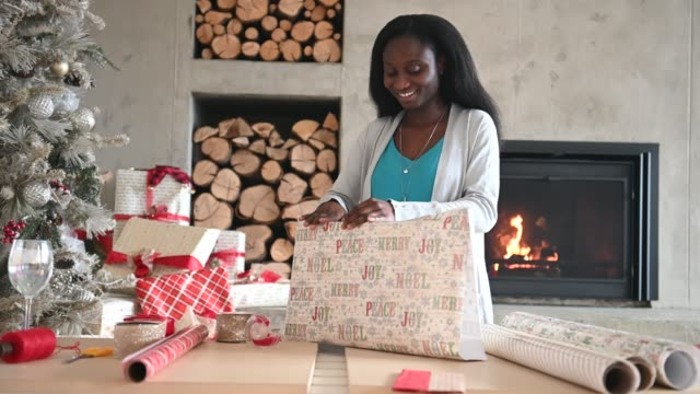 Afro American Young Woman Wrapping Christmas Gift Alone Home By Fireplace and Christmas Tree