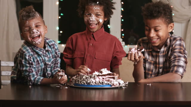 Afro boy's face smashing cake. video