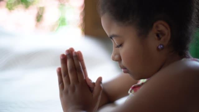 afro dziecko modląc się w domu - modlić się filmów i materiałów b-roll