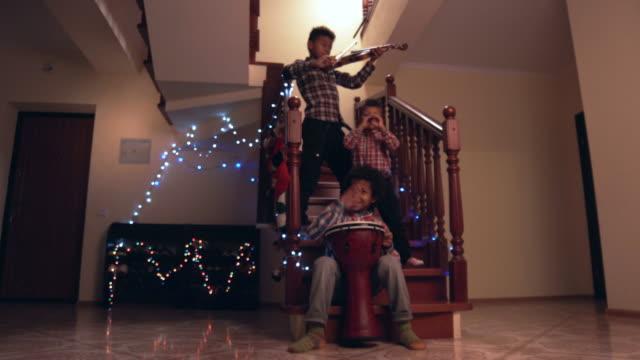 stockvideo's en b-roll-footage met afro kinderen spelen drie instrumenten. - christmas tree
