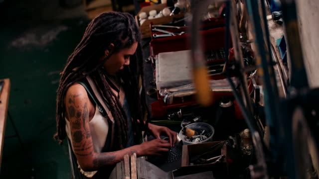Afro craftswoman assembling bicycle parts at her work bench video