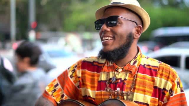 afro nedstigningen hipster mannen med gitarr utomhus - akustisk gitarr bildbanksvideor och videomaterial från bakom kulisserna