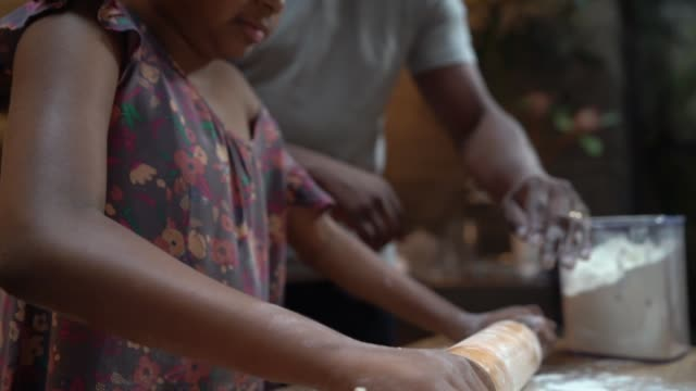 Afro father teaching his daughter how to cook at home