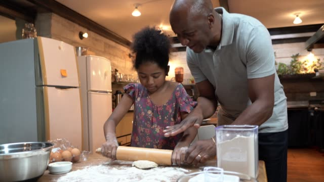 vídeos de stock e filmes b-roll de afro father teaching his daughter how to cook at home - baking bread at home