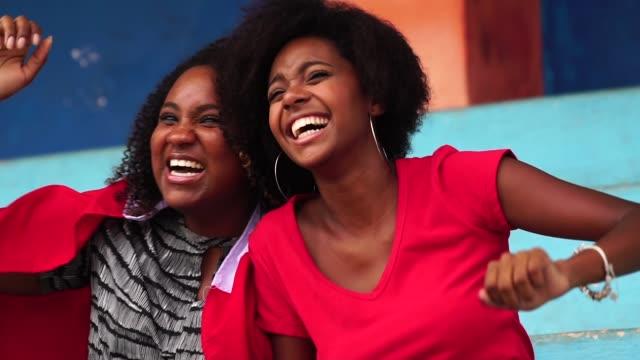 afro vänner titta på en fotbollsmatch - afro bildbanksvideor och videomaterial från bakom kulisserna