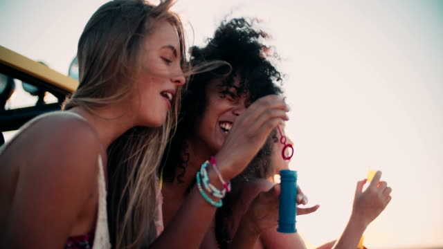Afro girl and friends blowing bubbles at the beach video