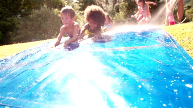 afro ragazza e amici giocando su un acquascivolo - tubo flessibile video stock e b–roll