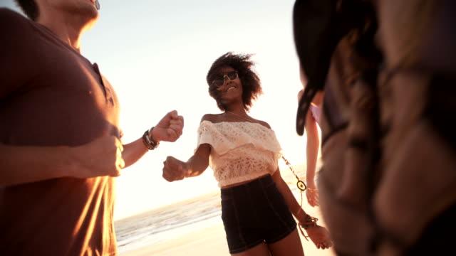 Ragazza Afro danza con il suo fidanzato in un tramonto beachparty - video