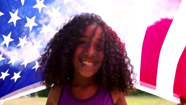 Afro girl happily holding an American flag Happy young Afro girl holding an American flag over her head and smiling positively in slow motion fourth of july videos stock videos & royalty-free footage