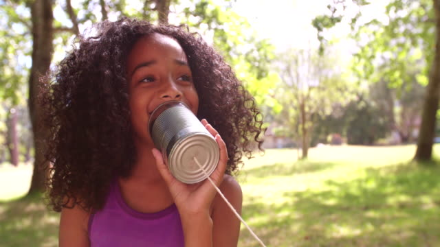 Afro girl talking into a tin can phone video