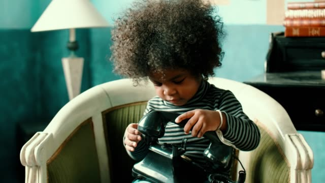 Afro girl using vintage phone