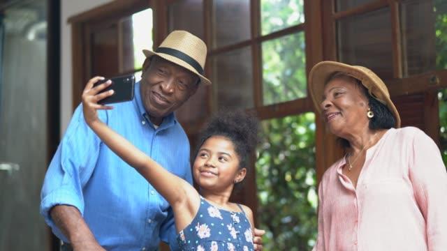 afro morföräldrar och barnbarn att ta selfies i ett hotellrum - aktiva pensionärer utflykt bildbanksvideor och videomaterial från bakom kulisserna